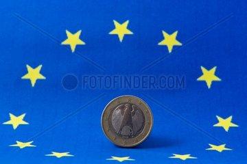 1-Euro-Muenze  im Hintergrund die europaeische Fahne  Deutschland  Europa