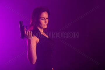 Frau mit einer Pistole im Nebel