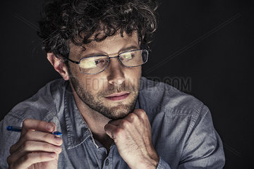 Man holding pen and looking down with hand under chin