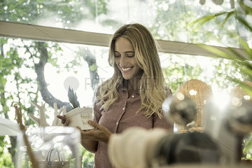 Young woman looking at potted plant in shop