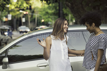 Young woman proudly showing friend keys to new car