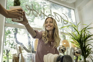 Woman buying potted plant in shop