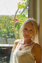 Mature woman leaning against window  portrait
