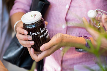 Woman holding jar of preserves  cropped