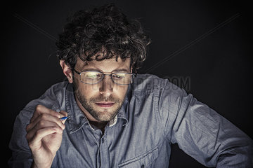Man holding pen and looking down in concentration