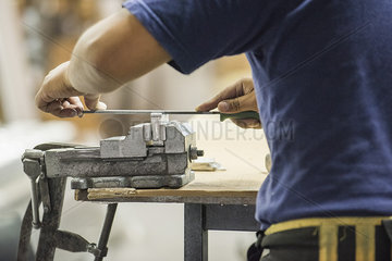 Man using file and vise in workshop  cropped