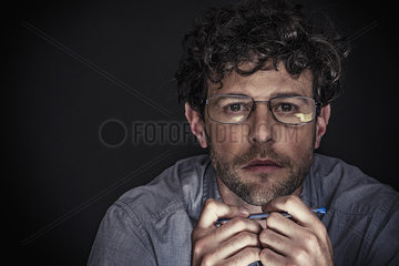 Man wearing glasses and holding pen  portrait