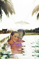 Couple relaxing together in resort swimming pool