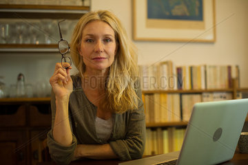 Mature woman sitting at home with laptop computer  portrait