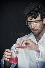 Chemist pouring liquid from test tube into beaker