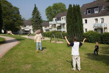 Vater spielt mit seinen Soehnen Fussball.