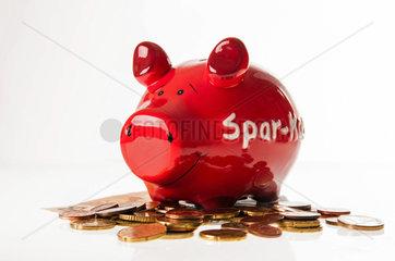 Rotes Sparschwein mit Muenzen