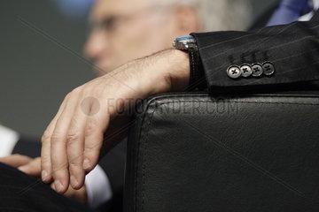 Gelassen auf der Armlehne eines Sessels liegende Hand