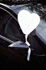 Luftballon in Herzform an einem Auto