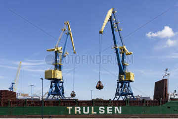 Two cranes unload a freighter in the port of Wismar