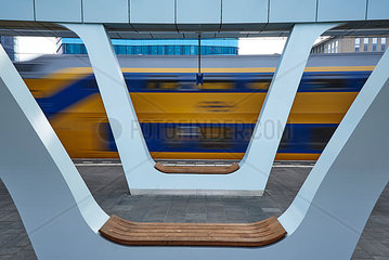 Netherlands  Arnheim  benches at platform of central station with train passing by in the background