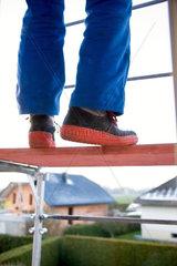Handwerker im Blaumann balanciert auf einem Baugeruest