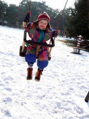 Kind auf einer Schaukel im Winter