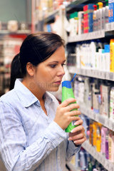 Junge Frau in einem Drogerie Markt bei Einkauf