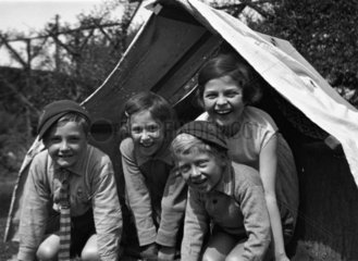 Four children smiling from the entrance of a tent  c 1920s.