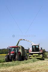 Landwirte bei der Herstellung von Grassilage auf einem Feld