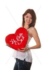 Junges Maedche verschenkt ein Liebesgeschenk Kissen in Herzform