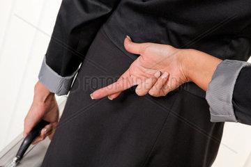 Business Frau mit im Ruecken ueberkreuzten Fingern