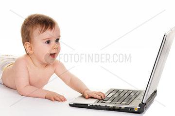 Kleines Kind in Windeln spielt mit einem Laptop Computer