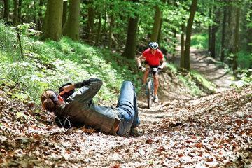Frau liegt am Boden und fotografiert einen Mountain Biker