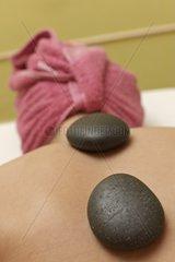 Behandlung Heisser Stein auf dem Ruecken einer Frau