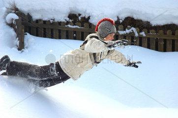 Bub laesst sich in den Schnee fallen