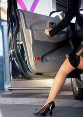 Damenbein aus einer Autotuere herausschauend