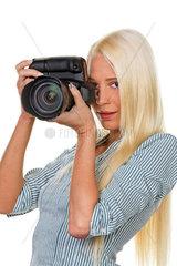 Junge Frau fotografiert mit einer digitalen Spiegelreflex Kamera