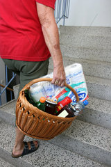 Seniorin mit schwerer Einkaufstasche