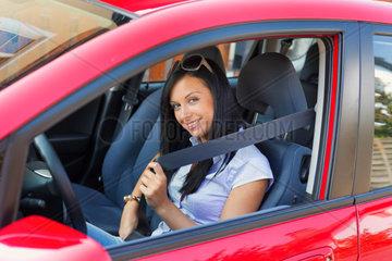 Junge Frau schnallt den Sicherheitsgurt in einem Auto an