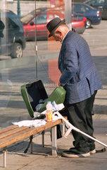 Mann mit Koffer und Kruecke