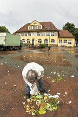 Mann sammelt Lebensmittelreste vom Boden auf