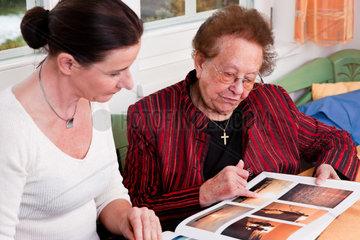 Eine alte Frau blaettert in einem Fotoalbum