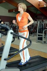 Frau in Fitness-Studio auf dem Laufband
