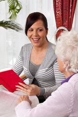 Eine junge Frau liest Senioren aus einem Buch vor