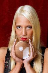 Junge Frau deutet die Zukunft aus einer Kristallkugel in ihren Haenden