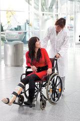 Junge Frau mit Gipsbein  Rollstuhl und Pflegerin