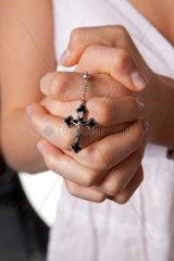 Junge Maedchen Haende zum Gebet gefaltet mit einem Kreuz