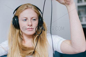 Junge blonde Frau hoert Musik ueber Kopfhoerer