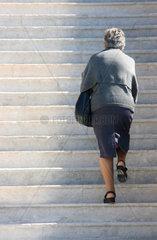 Frau steigt die Treppe hinauf