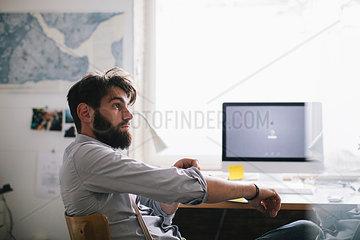 Junger Mann im Buero am Computer Arbeitsplatz