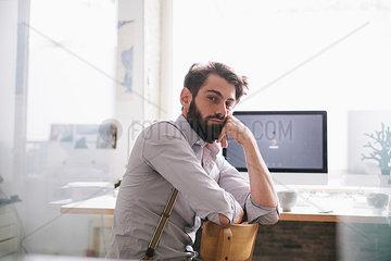 Mann mit Vollbart im Buero blickt skeptisch
