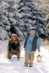 Kinder mit Rodel im Schnee