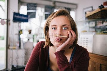 Junge Frau balanciert eine Bleistift zwischen Mund und Nase