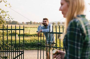 Junger Mann lehnt am Gartenzaun  Frau im Vordergrund